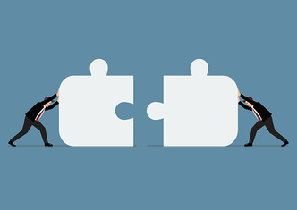 Businessmen pushing two jigsaw pieces together