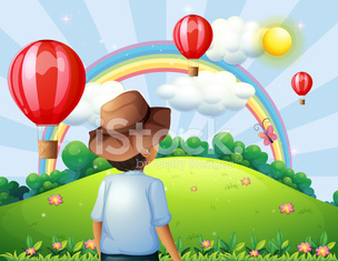 boy at the hilltop with flying balloons and a rainbow