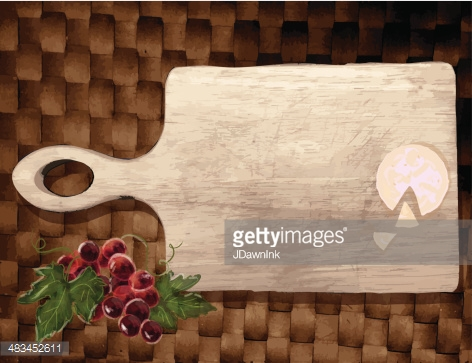 Cutting board with grapes and cheese on a weave background