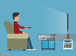 Man watches TV on sofa, before journal table