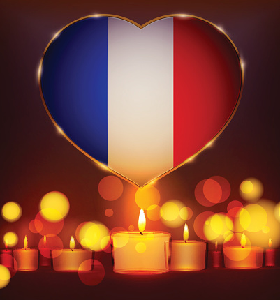 Candles in front of the national flag of France.