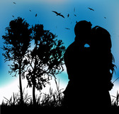 Couple Kissing Silhouette on Landscape with Tree Behind