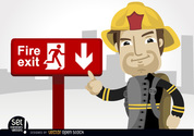 Fireman pointing fire exit sign
